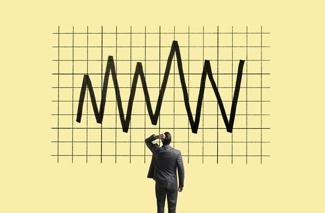 Man in suit stands facing a graph showing a line moving up and down