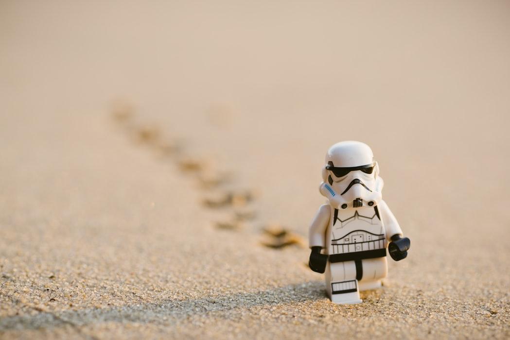 Lego stormtrooper walks towards the camera on sand