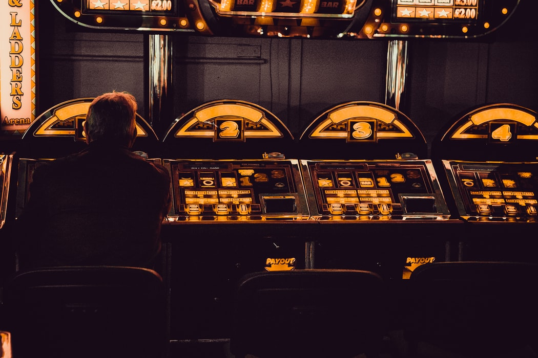 Man sits facing slot machines in a dimly lit room