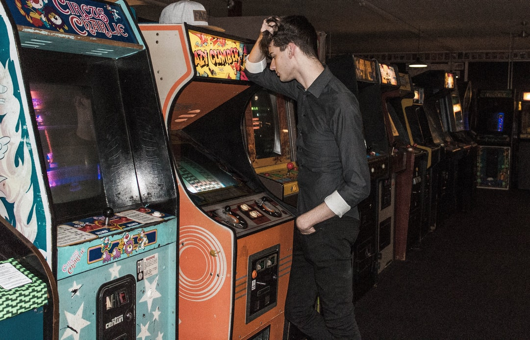 Man stands with hand on head in front of arcade machine
