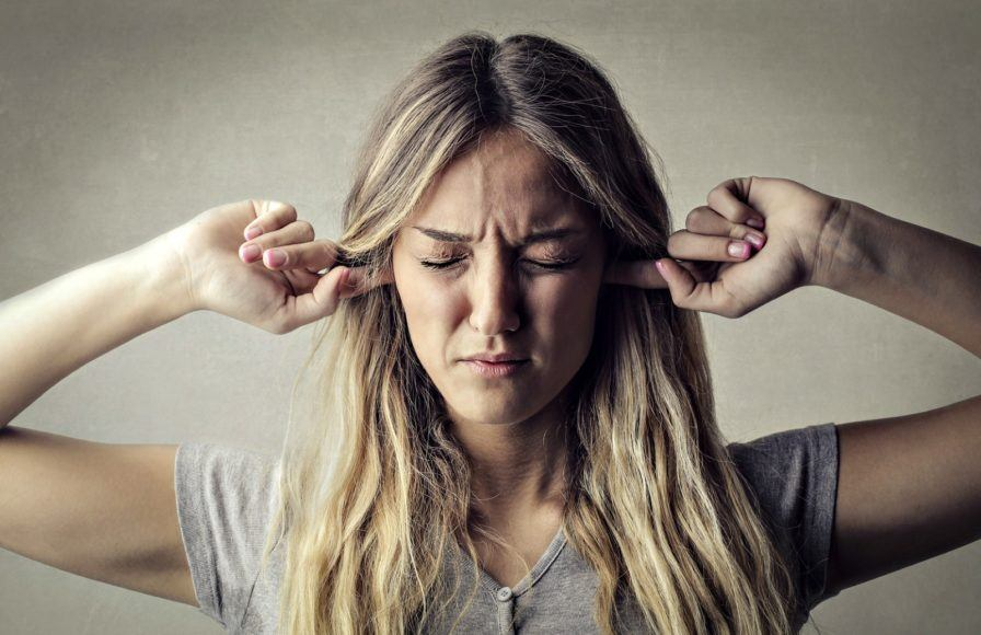 Woman closing her eyes putting her fingers in her ears