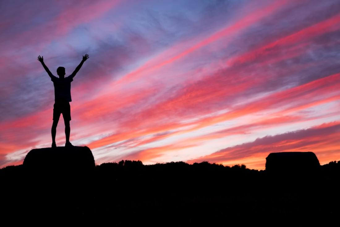 Man stands arms raised looking at sunset